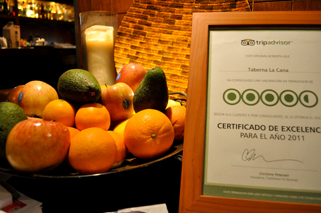 Entrance to restaurant with bowl of fruit and placard with tripadvisor certificate